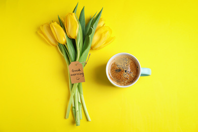 Aromatic coffee, beautiful flowers and GOOD MORNING wish on yellow background, flat lay