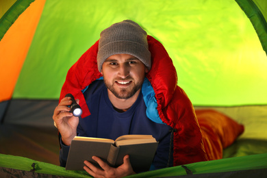 Young man with flashlight reading book in tent