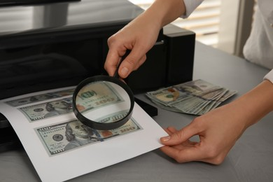 Counterfeiter examining sheet of paper with dollar banknotes at table indoors, closeup. Fake money concept