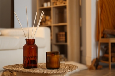 Aromatic reed air freshener and candle on wicker tray in room. Space for text