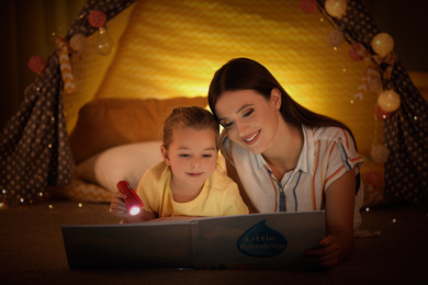 Mother and daughter with flashlight reading book at home