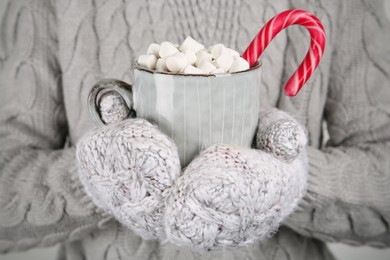 Woman in knitted mittens holding cup of delicious hot chocolate with marshmallows and candy cane, closeup