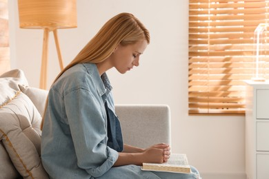 Religious young woman with Bible praying indoors. Space for text