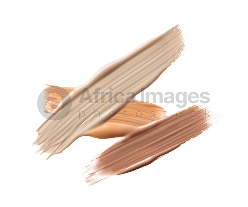 Different shades of liquid foundation on white background, top view