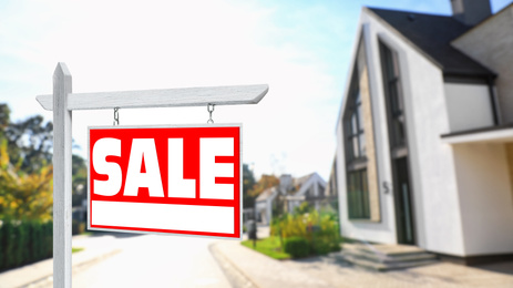 Red real estate sign with inscription SALE near house outdoors on sunny day, space for text