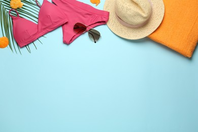 Flat lay composition with different beach objects on light blue background, space for text