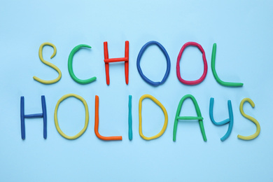 Phrase School Holidays made of modeling clay on light blue background, top view