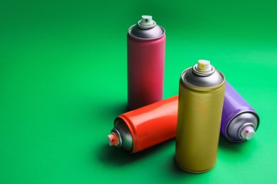 Cans of different graffiti spray paints on green background, space for text