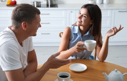 Man and woman talking while drinking tea at table in kitchen