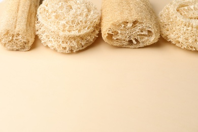 Natural shower loofah sponges on beige background. Space for text