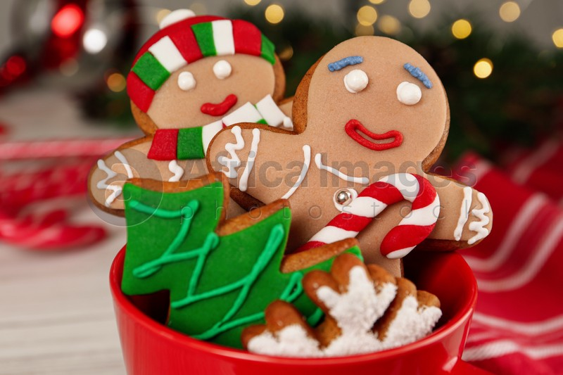 Delicious Christmas cookies in cup against blurred lights, closeup