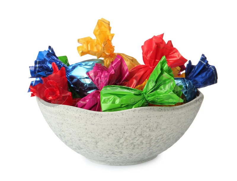 Bowl with candies in colorful wrappers isolated on white