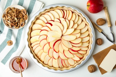 Raw traditional English apple pie in baking dish and ingredients on white table, flat lay