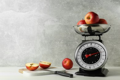 Kitchen scale with ripe apples on white wooden table. Space for text