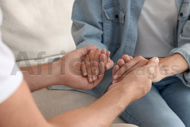 Religious people holding hands and praying together indoors, closeup