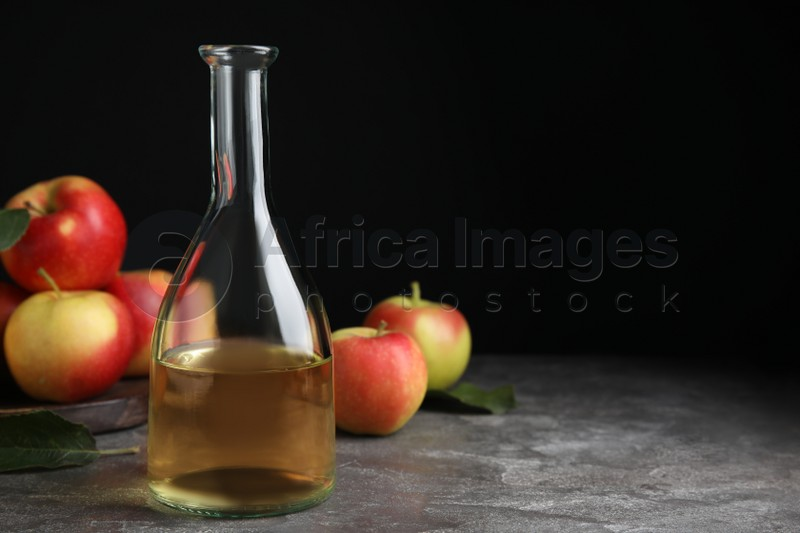 Natural apple vinegar and fresh fruits on grey table. Space for text