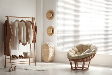 Modern dressing room interior with rack of stylish women's clothes