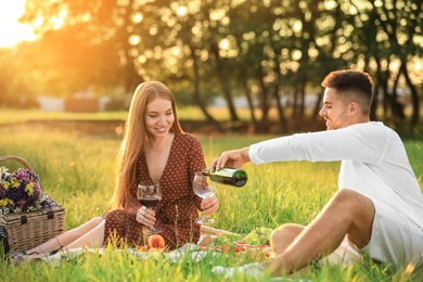 Young man and his girlfriend having picnic in green park