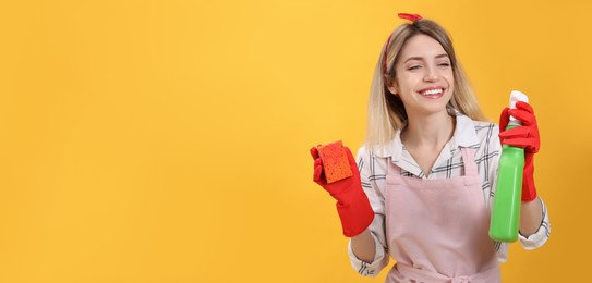 Young housewife with detergent and sponge on yellow background. Space for text