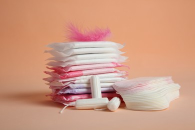 Menstrual pads with pink feather and other period products on pale orange background