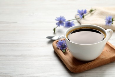 Cup of delicious chicory drink and flowers on white wooden table. Space for text