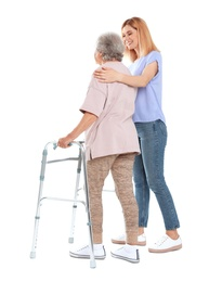 Caretaker helping elderly woman with walking frame on white background