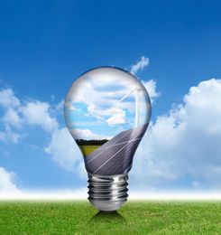 Alternative energy source. Light bulb with solar panels and wind turbines outdoors