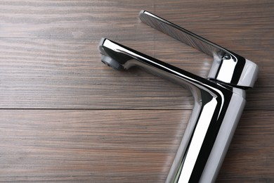Single handle water tap on wooden table, top view. Space for text