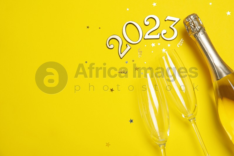 Happy New Year 2023! Flat lay composition with bottle of sparkling wine on yellow background, space for text