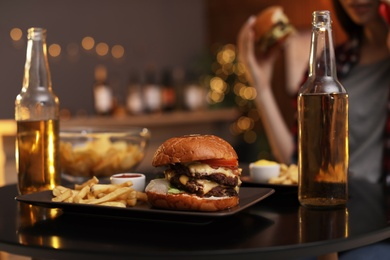 Tasty burger and french fries served on table in cafe
