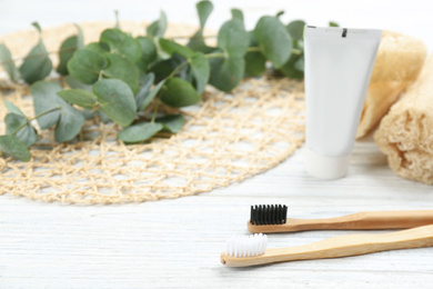 Bamboo toothbrushes on white wooden table. Space for text