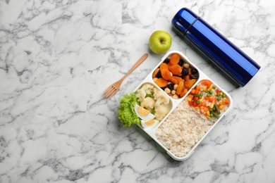 Thermos and lunch box with food on white marble, flat lay. Space for text