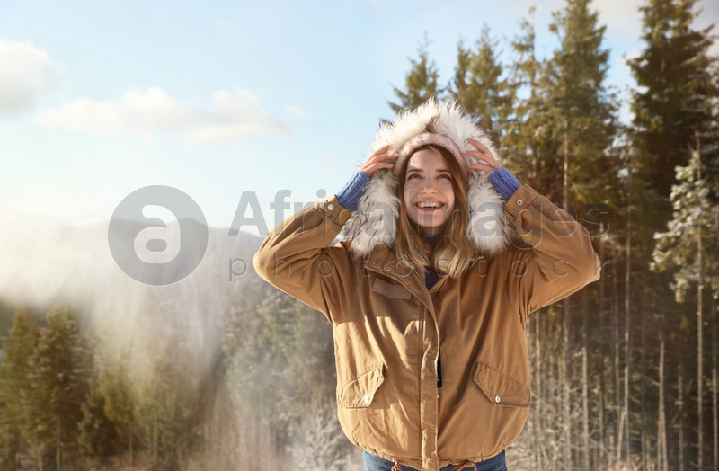 Happy young woman spending winter vacation in mountains
