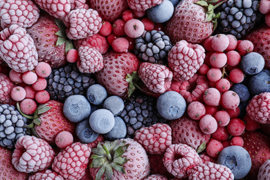 Mix of different frozen berries as background, top view