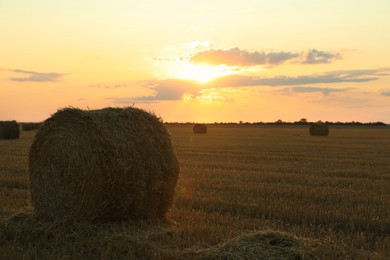 Beautiful view of agricultural field with hay bales at sunset