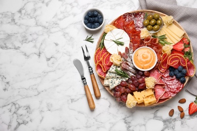 Wooden plate with different delicious snacks on white marble table, flat lay. Space for text
