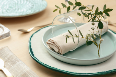 Elegant table setting with flowers and leaves, closeup