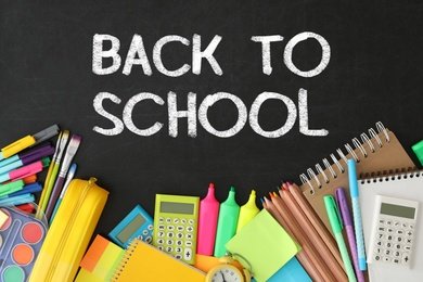 Text Back To School and different stationery on black chalkboard, flat lay