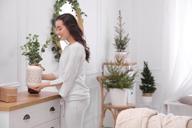 Woman decorating home interior with eucalyptus branches