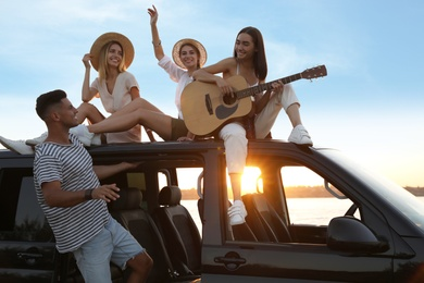 Happy friends with guitar near sea at sunset. Summer trip