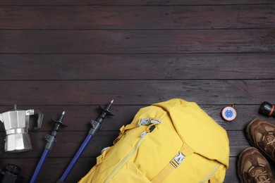 Flat lay composition with tourist backpack and other camping equipment on wooden background, space for text