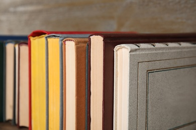 Stack of hardcover books on wooden background, closeup