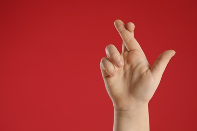 Child holding fingers crossed on red background, closeup with space for text. Good luck superstition