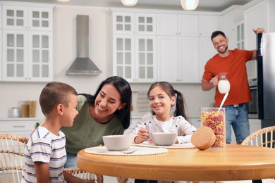 Happy family with children having fun during breakfast at home