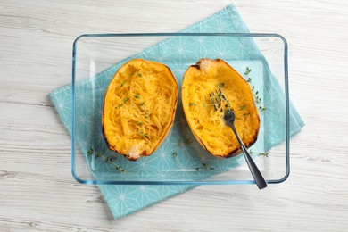 Halves of cooked spaghetti squash with thyme and fork in baking dish on white wooden table, top view