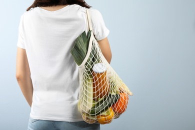 Woman holding mesh bag with fresh vegetables on grey background, closeup. Space for text