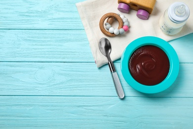 Flat lay composition with bowl of healthy baby food on light blue wooden table. Space for text