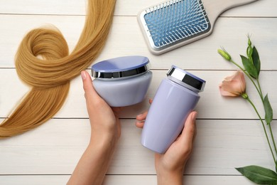 Woman holding hair care cosmetic products at white wooden table, top view