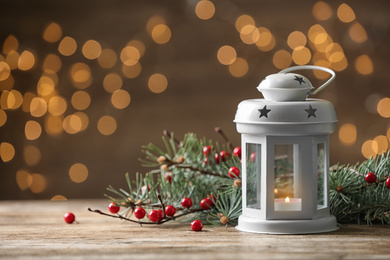 Composition with lantern and decorated fir branches on table against blurred background. Winter holidays