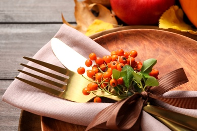 Table setting with rowan berries on wooden background, closeup. Thanksgiving Day